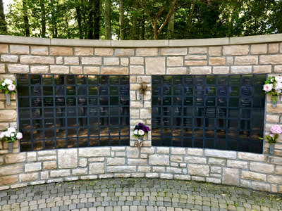 Photo of columbarium wall, a stone wall about 8 feet high with names inscribed on little black plaques.