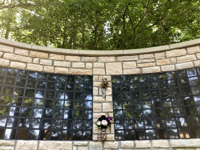 photo of columbarium wall, a stone wall with names inscribed on little black plaques